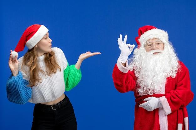 Vista frontal do papai noel junto com uma jovem fêmea em um modelo de férias de ano novo azul.