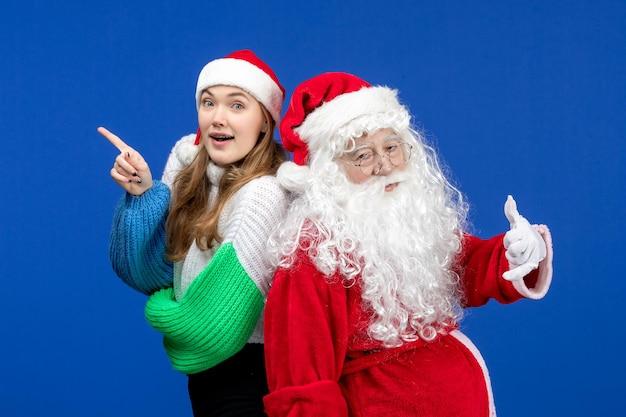 Vista frontal do papai noel junto com uma jovem fêmea parada na mesa azul, feriado natal