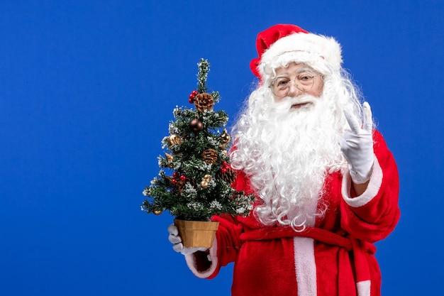Vista frontal do papai noel segurando a pequena árvore de ano novo na mesa azul natal ano novo