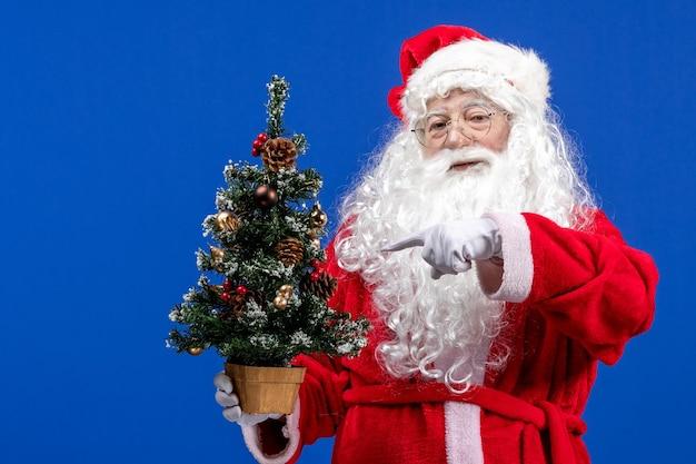 Vista frontal do papai noel segurando a pequena árvore de ano novo no azul de natal ano novo