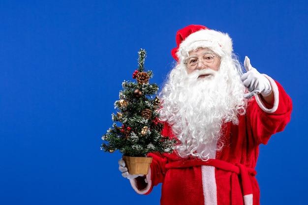 Vista frontal do papai noel segurando a pequena árvore de ano novo no chão azul, cor de natal de ano novo