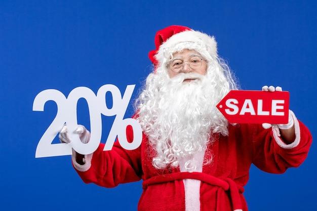 Vista frontal do papai noel segurando a venda e escritos sobre a cor azul na neve feriado ano novo natal