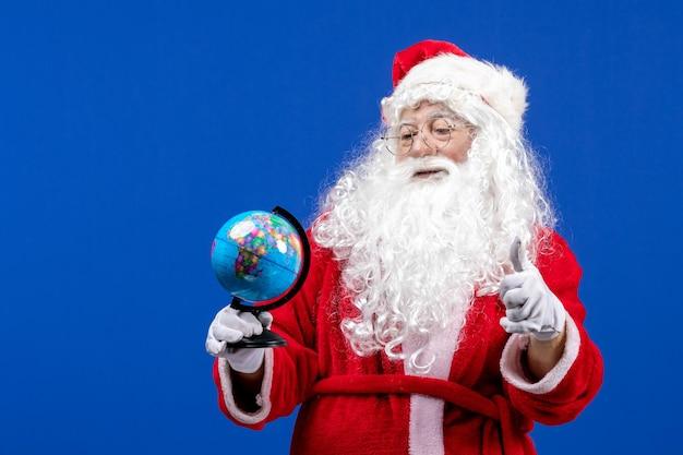 Vista frontal do papai noel segurando o pequeno globo terrestre no feriado de natal de cor azul do ano novo