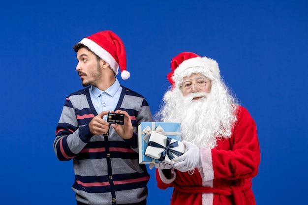 Vista frontal do papai noel segurando presentes e jovem segurando o cartão do banco em um natal azul