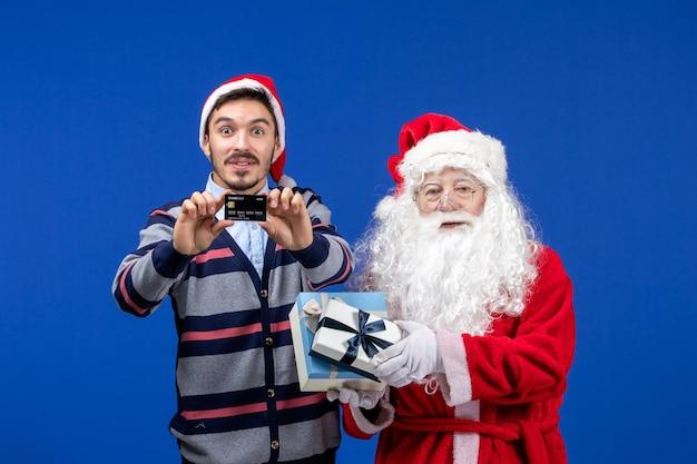 Vista frontal do papai noel segurando presentes e jovem segurando o cartão do banco na emoção azul do natal novo