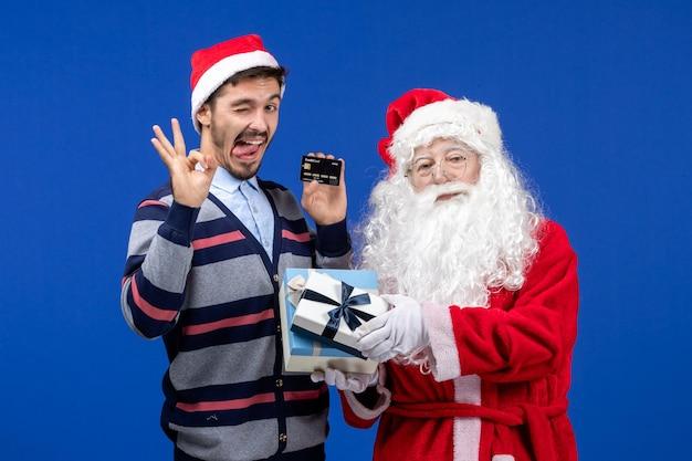 Vista frontal do papai noel segurando presentes e jovem segurando o cartão do banco na mesa azul, feriado de natal