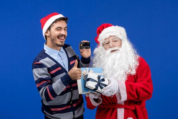 Vista frontal do papai noel segurando presentes e jovem segurando o cartão do banco no feriado azul