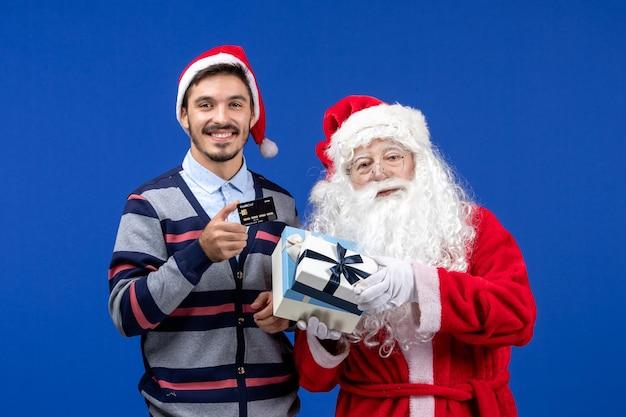 Vista frontal do papai noel segurando presentes e jovem segurando um cartão do banco no azul do feriado de natal