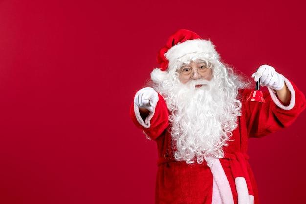 Vista frontal do papai noel segurando sininho na mesa vermelha emoção presente feriado de natal