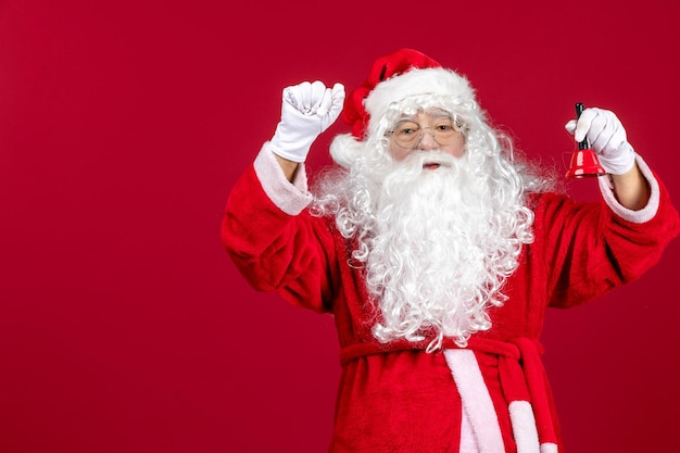 Vista frontal do papai noel segurando sininho na mesa vermelha natal emoção feriado