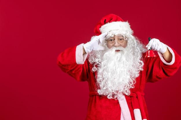 Vista frontal do papai noel segurando sininho no feriado de emoção de ano novo de natal vermelho