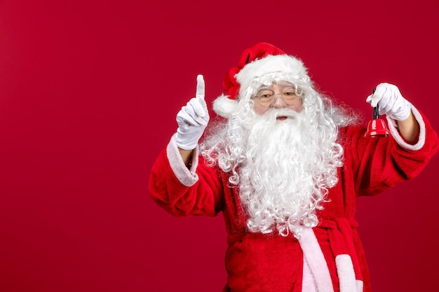 Vista frontal do papai noel segurando sininho no feriado de presente de ano novo de emoção vermelha
