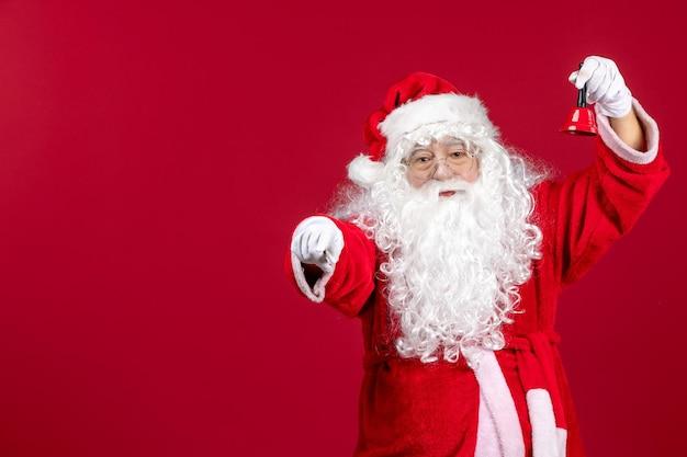 Vista frontal do papai noel segurando sininho no presente vermelho, emoção, feriado de ano novo