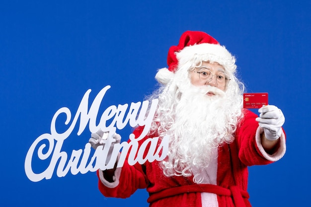 Vista frontal do papai noel segurando um cartão do banco e uma escrita de feliz natal no presente de feriado de cor azul