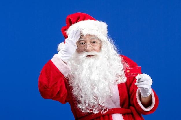 Vista frontal do papai noel segurando um cartão do banco vermelho na cor azul do ano novo, feriados de natal