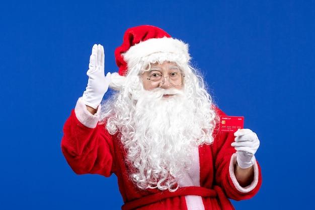 Vista frontal do papai noel segurando um cartão do banco vermelho na mesa azul no feriado de natal