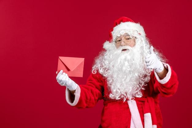 Vista frontal do papai noel segurando um envelope com uma carta de desejo de uma criança na emoção vermelha presente de natal