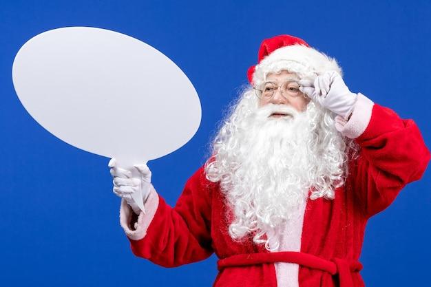 Vista frontal do papai noel segurando uma grande placa branca na cor azul, neve, feriado natal