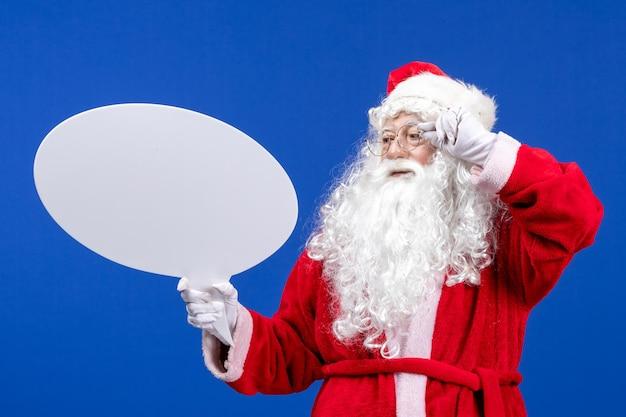 Vista frontal do papai noel segurando uma grande placa branca no chão azul neve férias cor natal