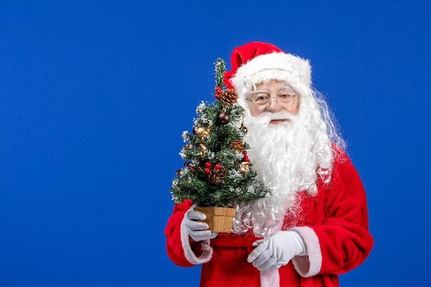 Vista frontal do papai noel segurando uma pequena árvore de ano novo na cor azul da neve natal ano novo