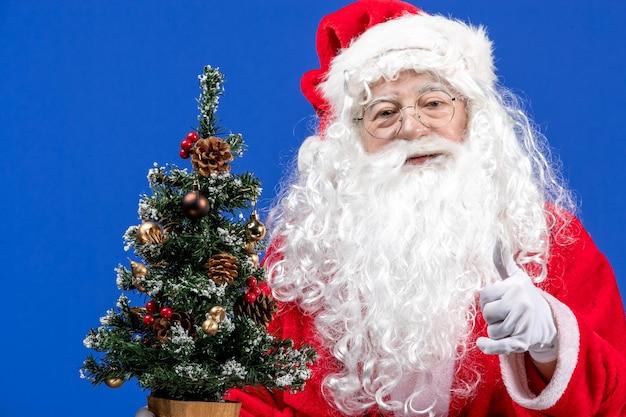 Vista frontal do papai noel segurando uma pequena árvore de ano novo na neve azul de natal de ano novo