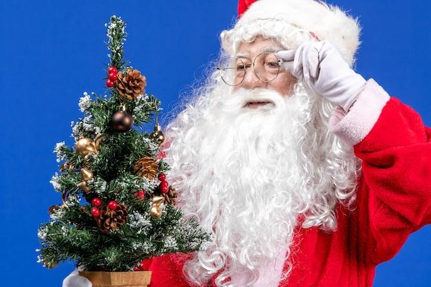 Vista frontal do papai noel segurando uma pequena árvore de ano novo no chão azul cor da neve natal ano novo