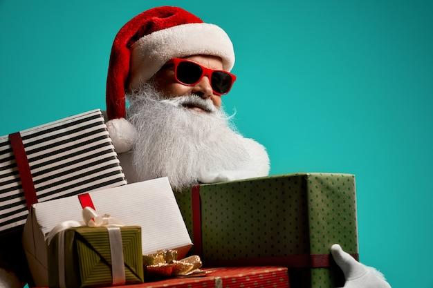 Vista frontal do papai noel sorridente com barba branca, aparecendo o polegar. retrato isolado do homem sênior bonito em traje de natal e óculos posando conceito de férias.