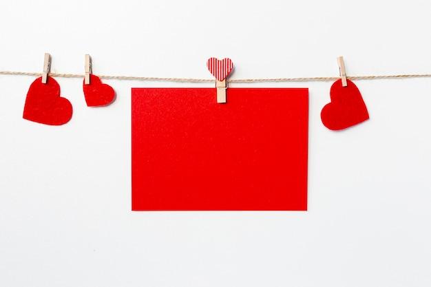 Vista frontal do papel e corações na corda para dia dos namorados
