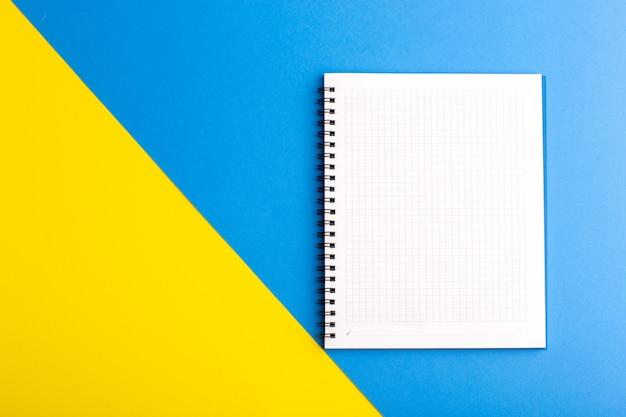 Vista frontal do papel em branco do caderno azul aberto na superfície azul amarela
