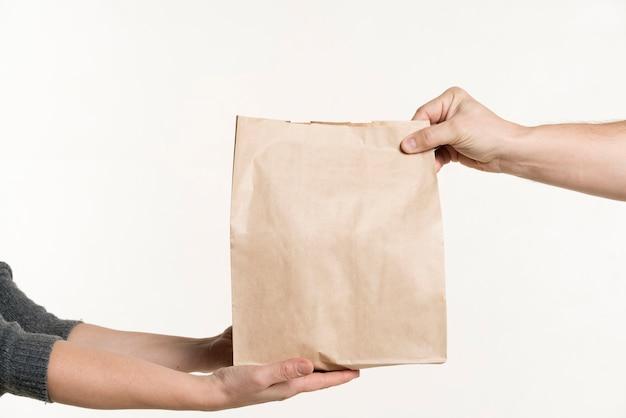 Vista frontal do par de mãos segurando um saco de papel