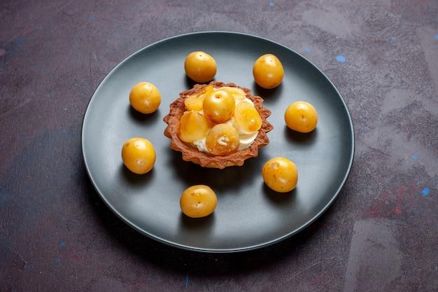 Vista frontal do pequeno bolo cremoso com cerejas frescas dentro do prato na superfície escura