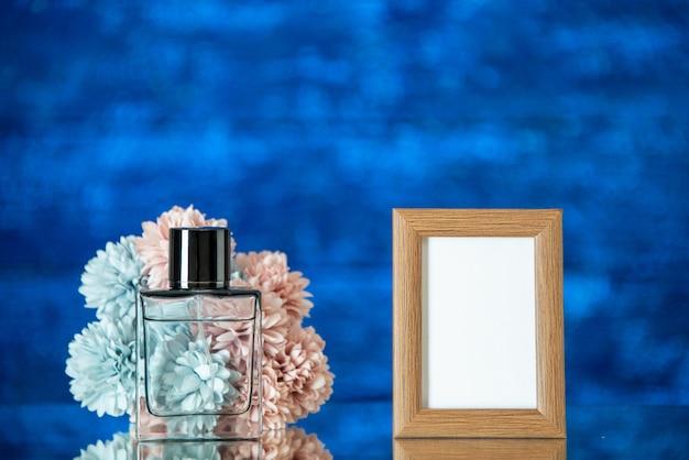 Vista frontal do perfume feminino marrom claro moldura flores em fundo azul escuro