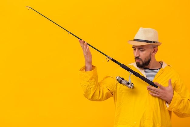 Vista frontal do pescador apreciando sua vara de pescar