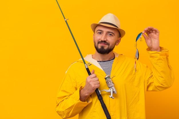 Vista frontal do pescador posando com vara de pesca e isca