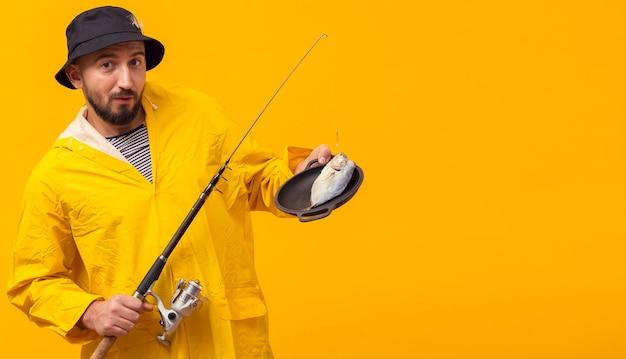 Vista frontal do pescador segurando a vara de pescar com as capturas no prato