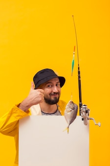 Vista frontal do pescador segurando a vara de pescar e dando polegares para cima