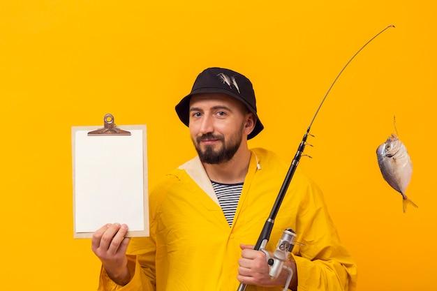 Vista frontal do pescador segurando a vara de pescar e o bloco de notas