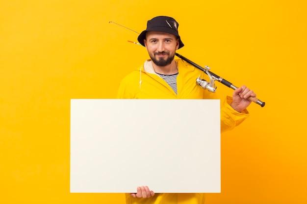 Vista frontal do pescador segurando o cartaz em branco