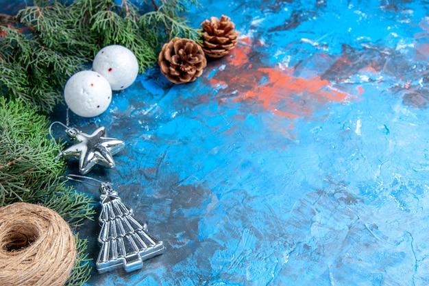 Vista frontal do pinheiro galhos de pinecones fio de palha bolas de árvore de natal em fundo azul-vermelho com espaço livre