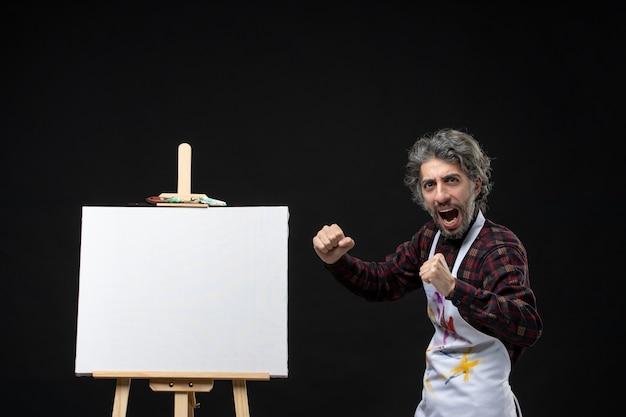 Vista frontal do pintor com cavalete exultando na parede preta