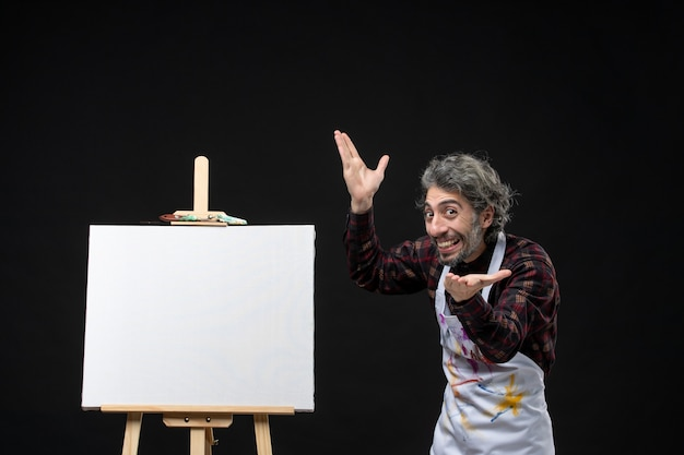 Vista frontal do pintor masculino com cavalete na parede preta