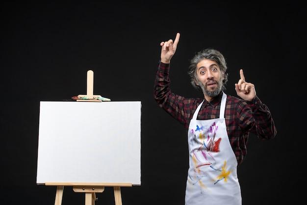 Vista frontal do pintor masculino com cavalete para desenhar na parede preta