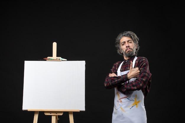 Vista frontal do pintor masculino com cavalete posando na parede preta