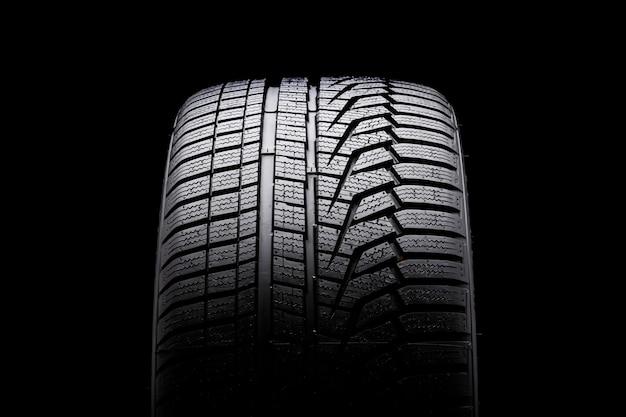 Vista frontal do pneu de inverno. padrão de piso assimétrico. inflar pneus para a temporada. fundo preto close-up.