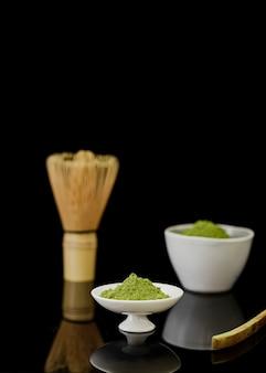 Vista frontal do pó de chá matcha com batedor de bambu e espaço para texto