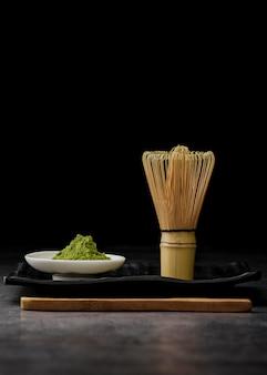 Vista frontal do pó de chá matcha com batedor de bambu