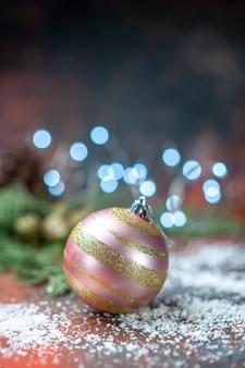 Vista frontal do pó de coco da bola da árvore do natal na luz escura do natal