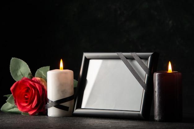 Vista frontal do porta-retrato com vela e flor no escuro