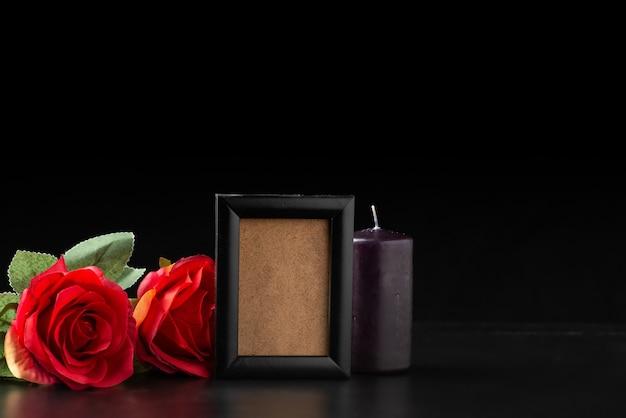 Vista frontal do porta-retrato vazio com rosas vermelhas em preto