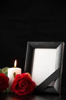 Vista frontal do porta-retratos com flores vermelhas no preto